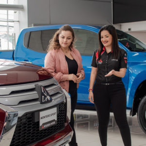 Vendedores de carros asesorando sobre primer auto - Mitsubishi Motors
